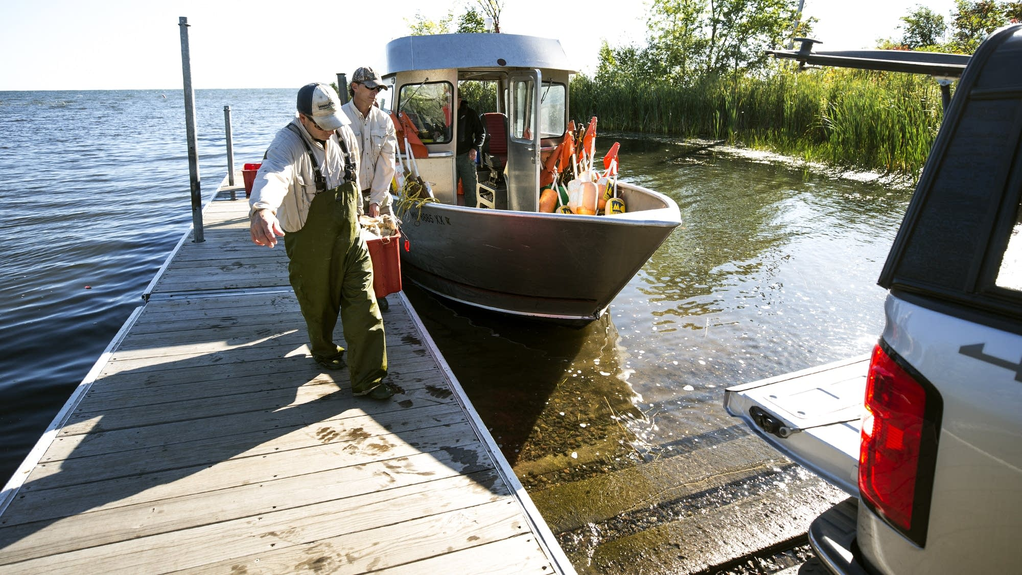 DNR employees Kris Nissen, front, and Greg Berg carry in their catch.