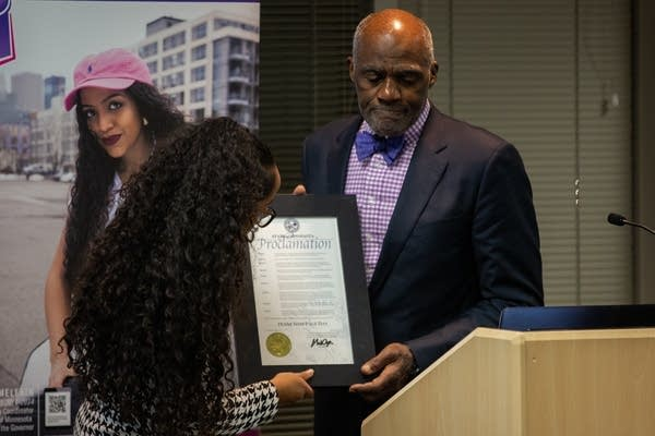 Justice Alan Page holds a proclamation from Gov. Mark Dayton