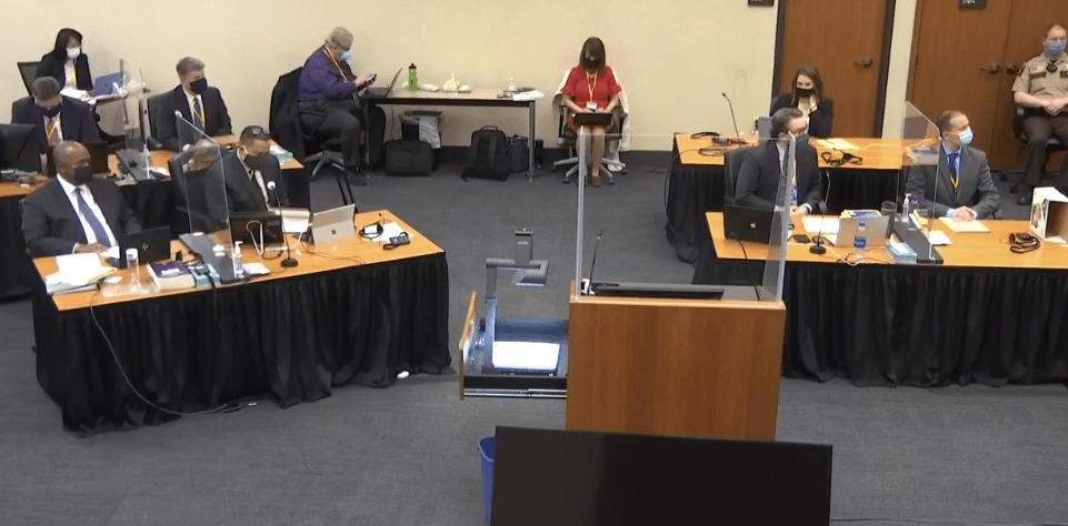 People sit behind desks in a courtroom.