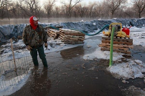 Jonathan Robbins checks a levee pump