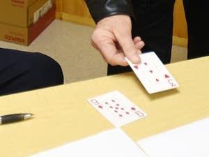 Larson laid down his card next to incumbent mayor Allen's winning card.