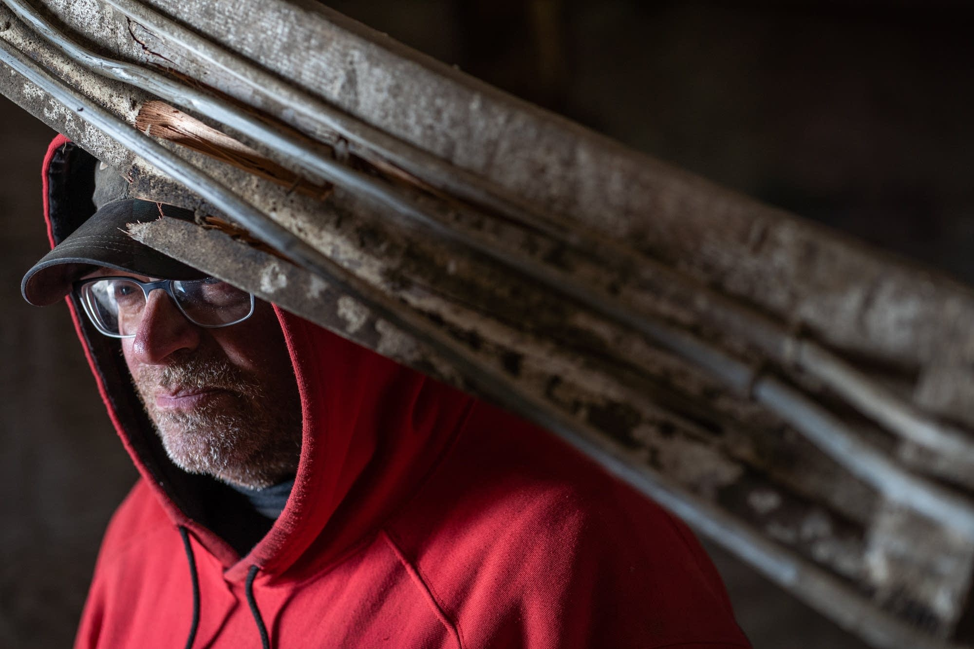 Dairy farmer Dave Alberts rests his head on a broken beam.