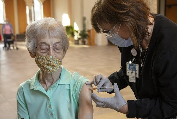 A nurse administers a vaccination shot to a woman sitting.
