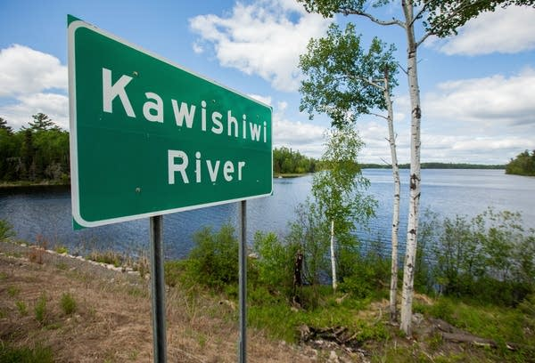 A green sign is located along the banks of the Kawishiwi River