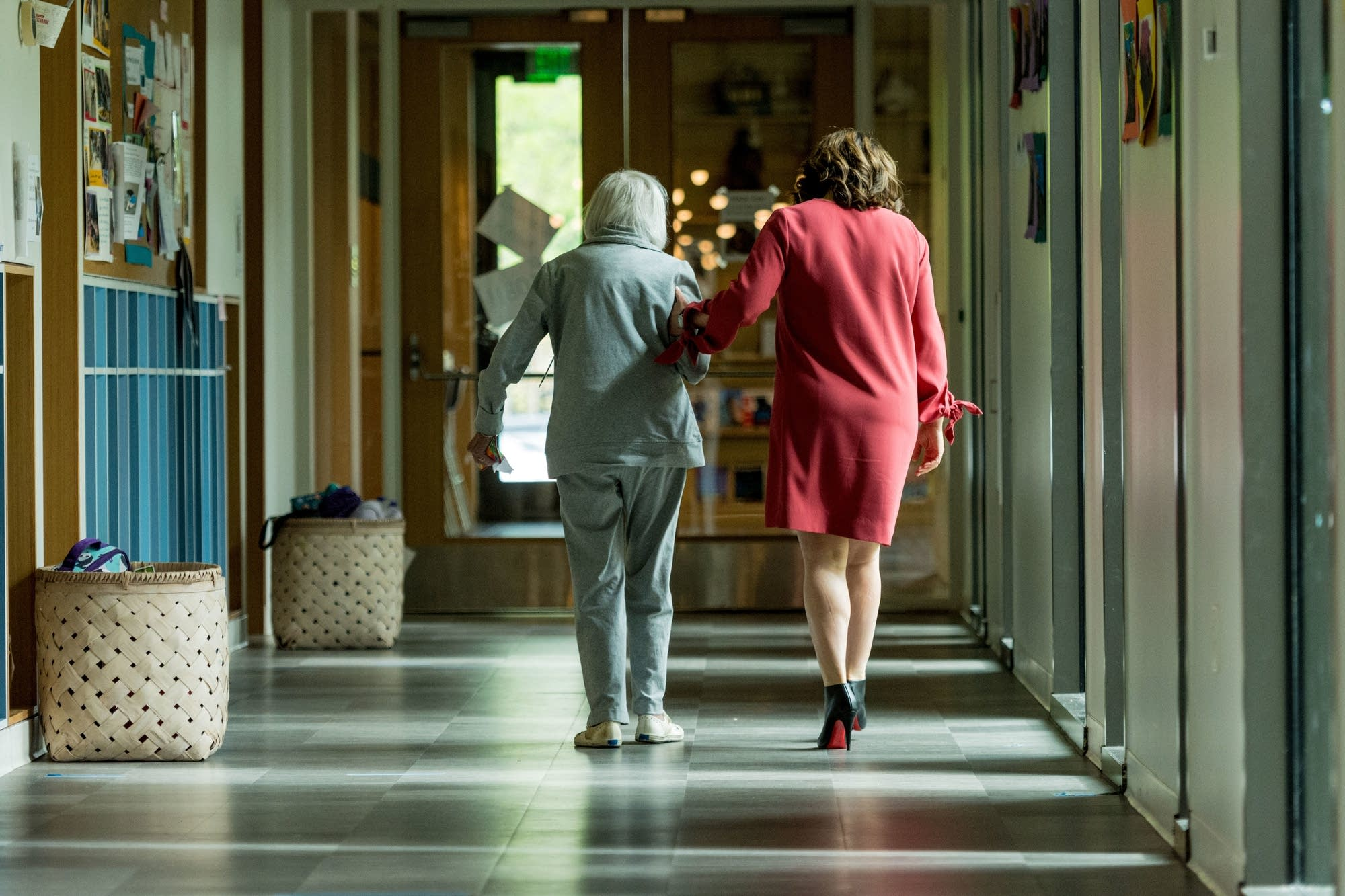 Ruth Knelman, left, and Rabbi Marcia Zimmerman walk down the hall.