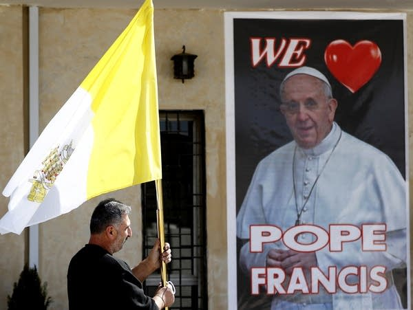 A Christian priest holds a Vatican flag
