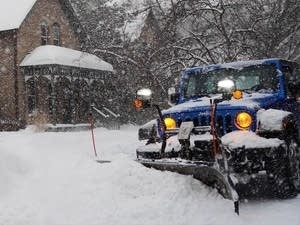 A Minneapolis snow plow clears a sidewalk.