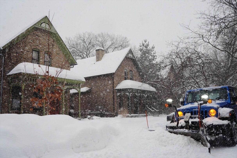 A Minneapolis snow plow clears a sidewalk.