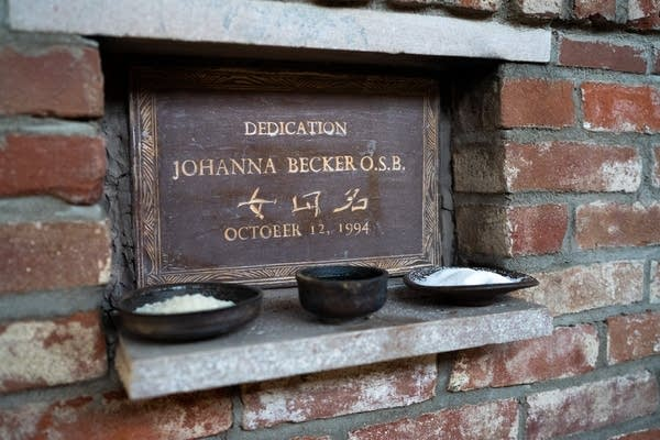 Rice, sake and salt sit in front of a plaque.