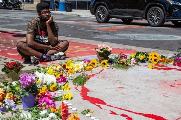 A man sits on the sidewalk next to a circle of flowers.