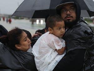 Evacuees make their way to dry land.
