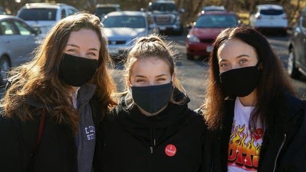 Three people wearing face masks.