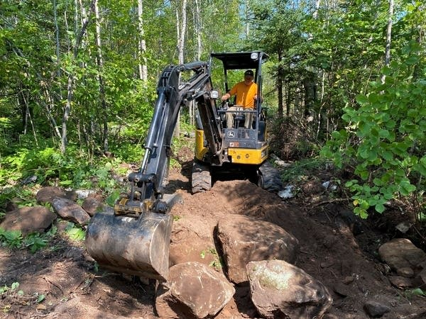 A person uses an excavator to move rocks.
