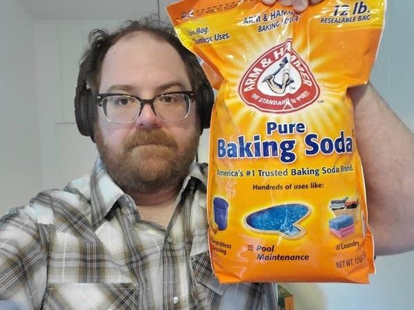 Andrew (white 43 year old man w glasses) holding 12 lb bag of baking soda.
