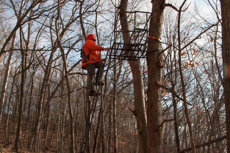 Jacob Zeuske climbs into a deer stand.