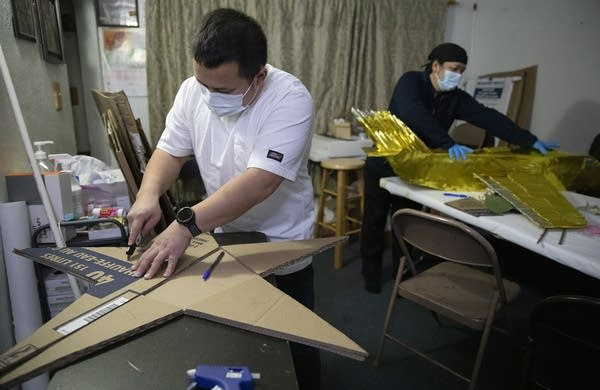 A man wearing a face mask cuts large cardboard into a star.