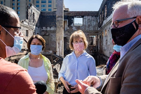 Four people stand in front of the ruins of a building.