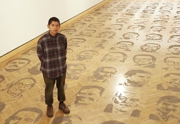 The artist stands on a wooden floor covered with printed faces.