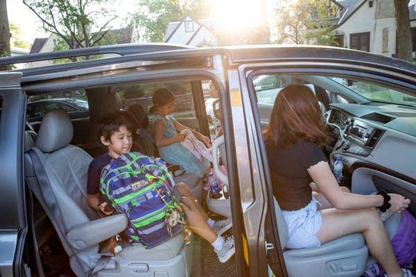 Three children sit in a minivan.