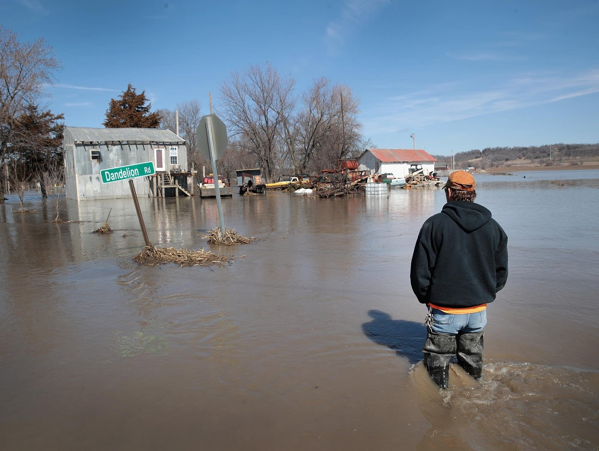 Brian Nutchler walks through floodwaters to his home