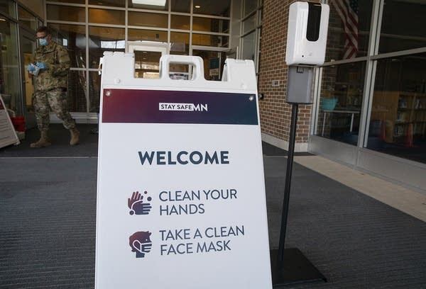 """A sign reads """"Welcome. Clean your hands. Take a clean face mask."""""""