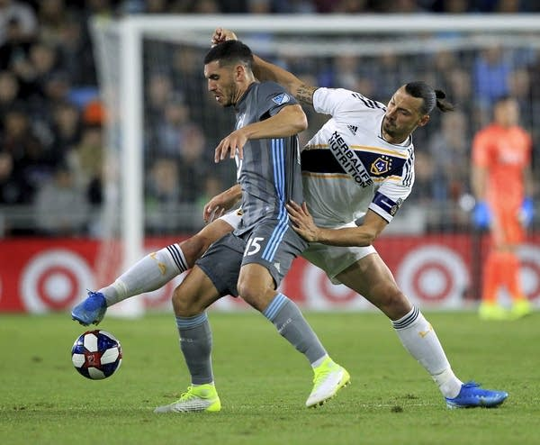 Two soccer players battle for the ball
