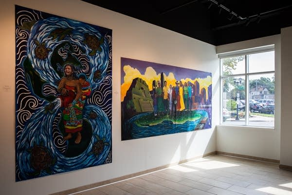 Two murals hang in a lobby.