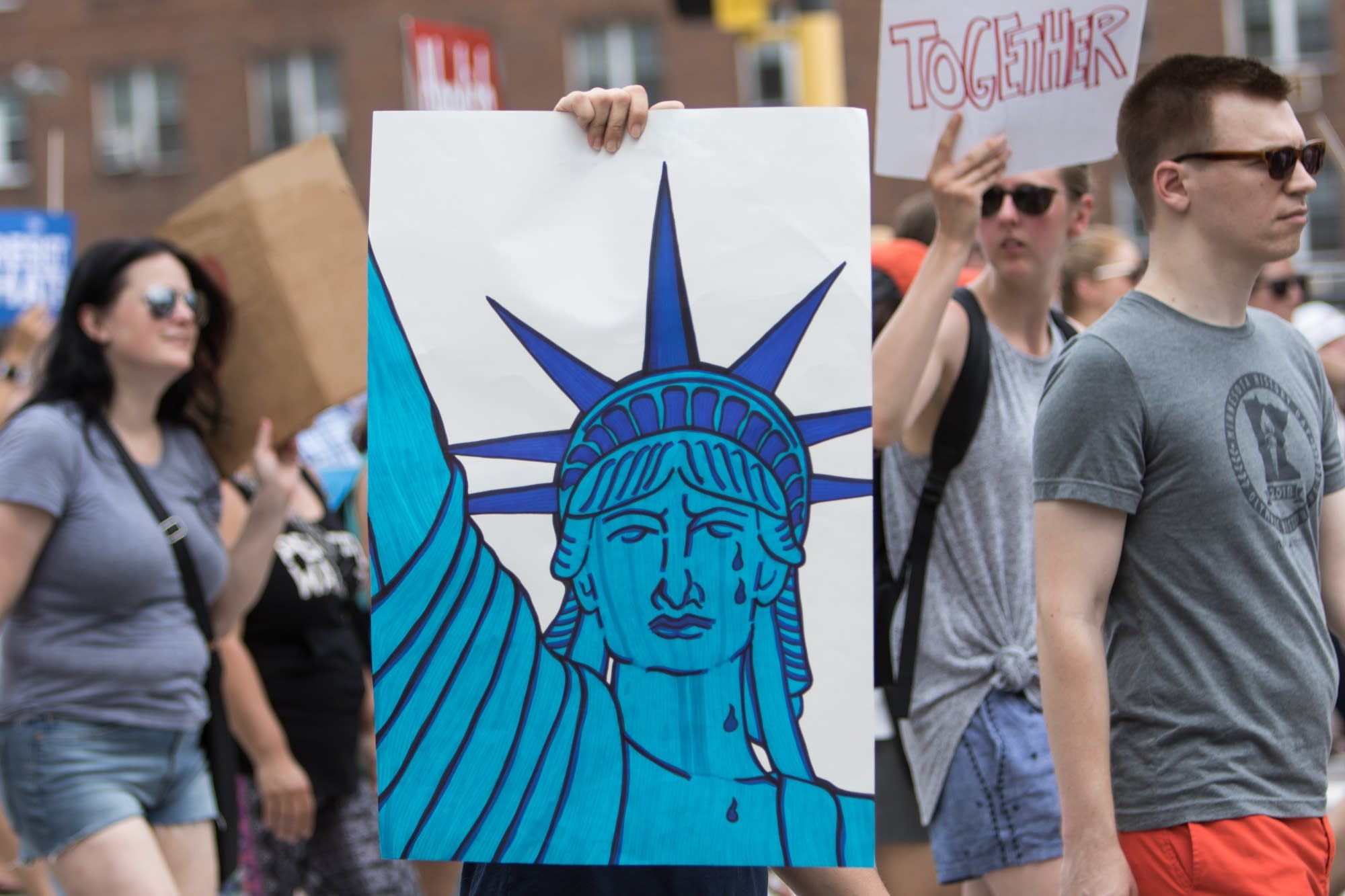 A protester holds a poster depicting a crying Statue of Liberty.