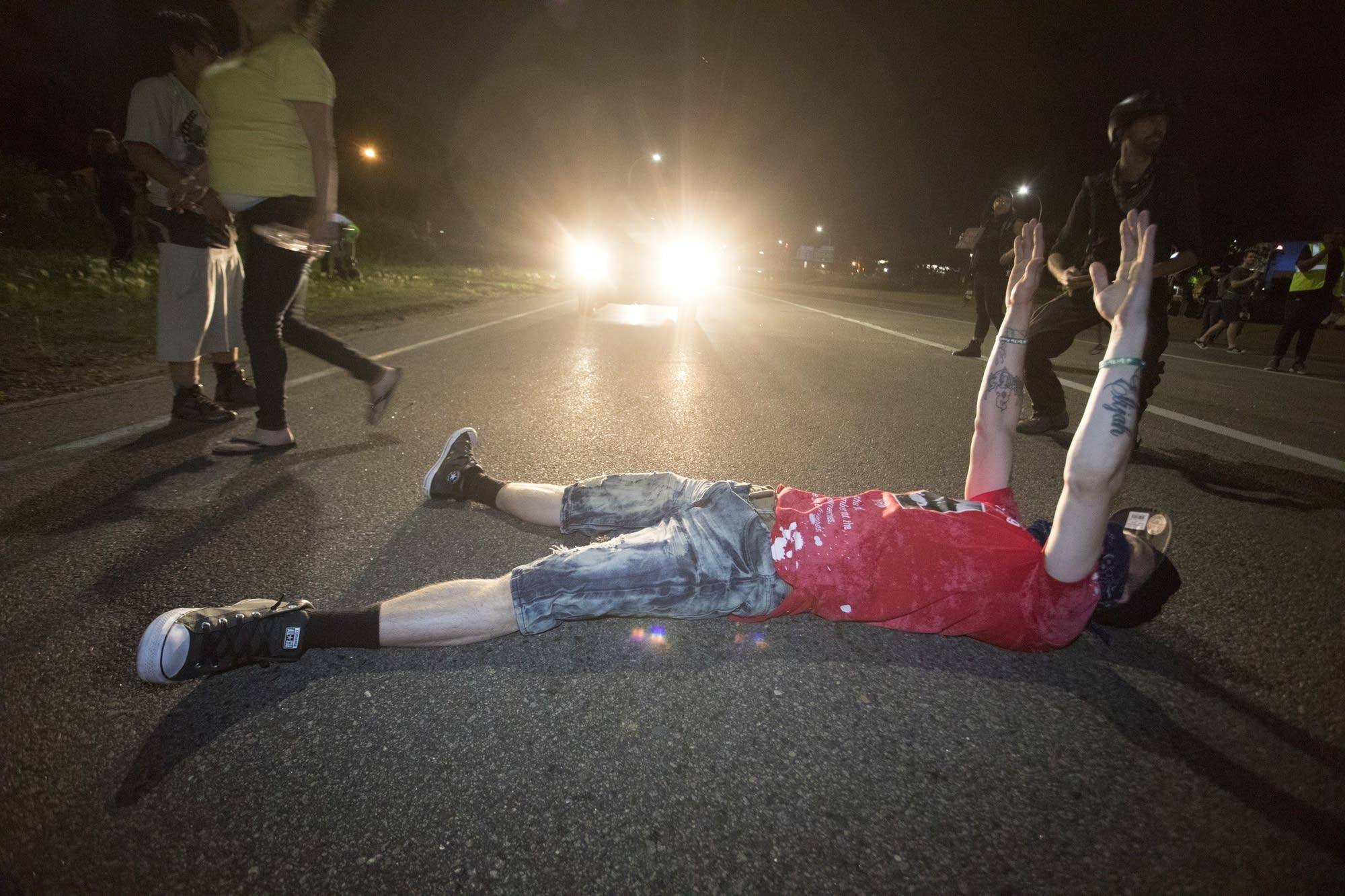 A protester lay on the road in front of a vehicle.