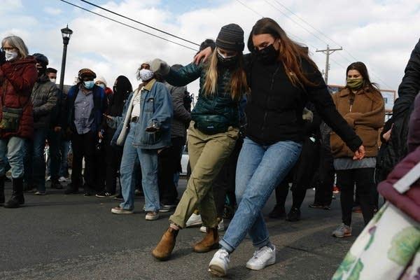 People dance in the street.