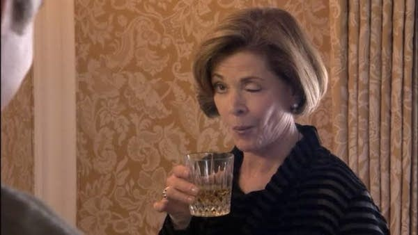Actress Jessica Walter as Lucille Bluth drinking cocktail and winking