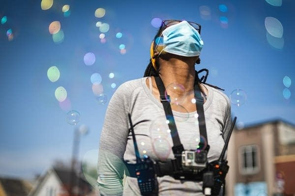 A woman looks up at the sky during a street festival.