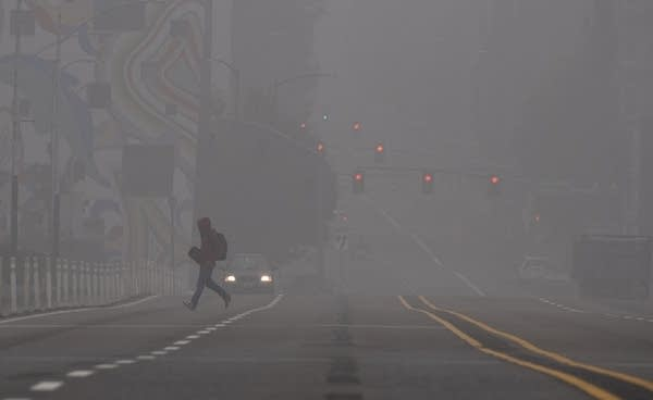 A man crosses a street amid smoky air.