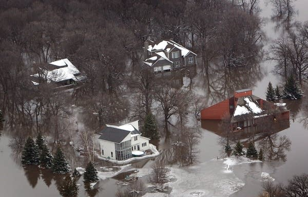 Homes are surrounded by ice and flood water