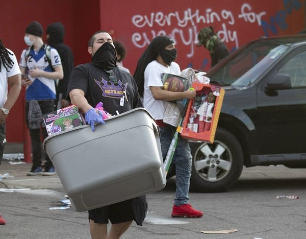 People carry items out of a store.