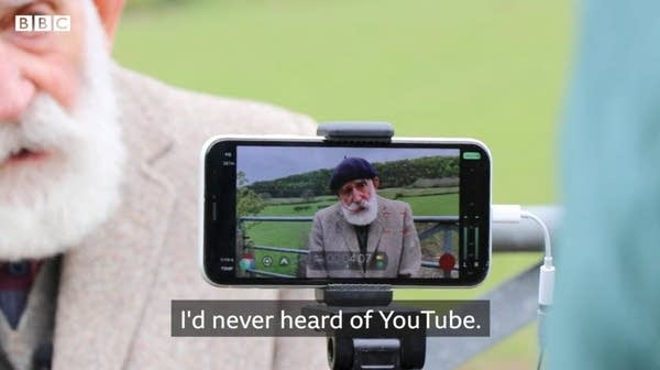 Smartphone filming an older white man w/ big white beard