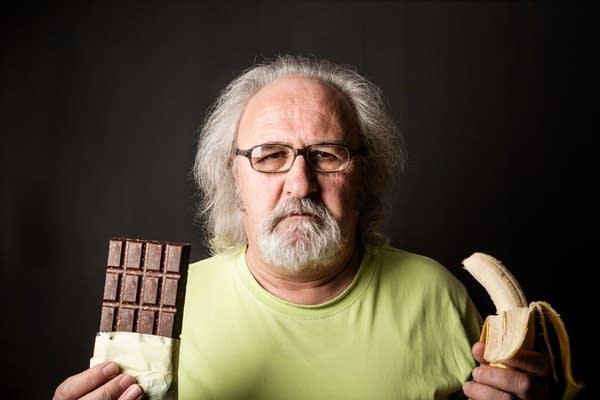 Older white man w/ Long hair, looking glum holding banana and chocolate