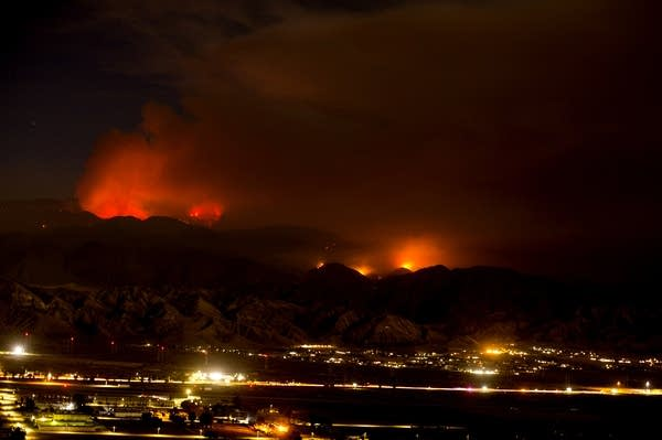 The Apple Fire burns behind mountains.