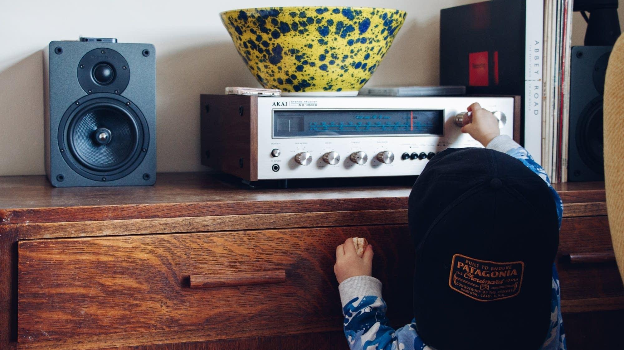 Child adjusting radio knob