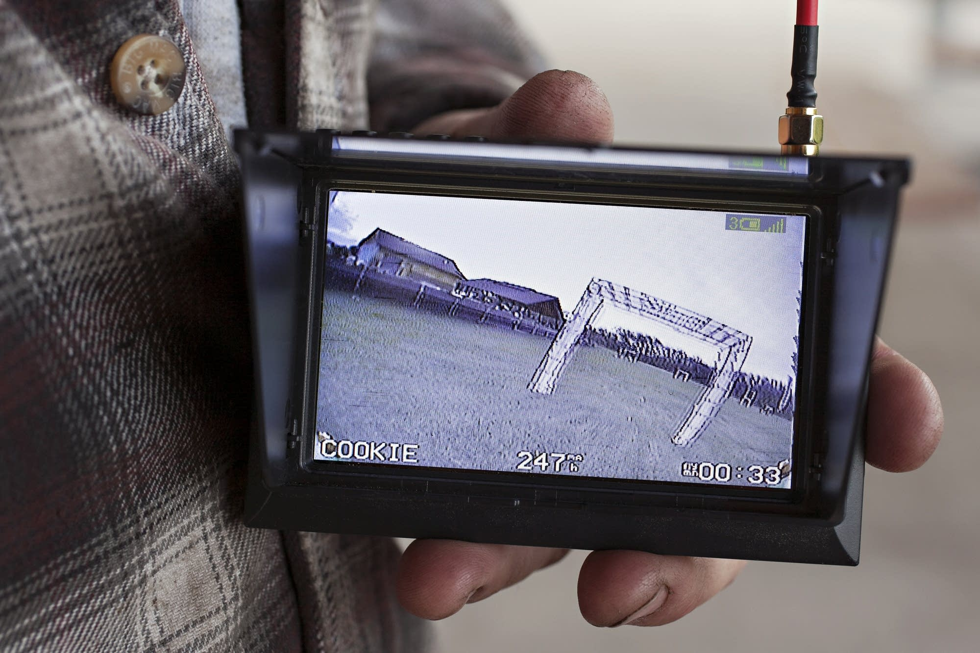 A small monitor displays the video from a camera on board a tiny aircraft.