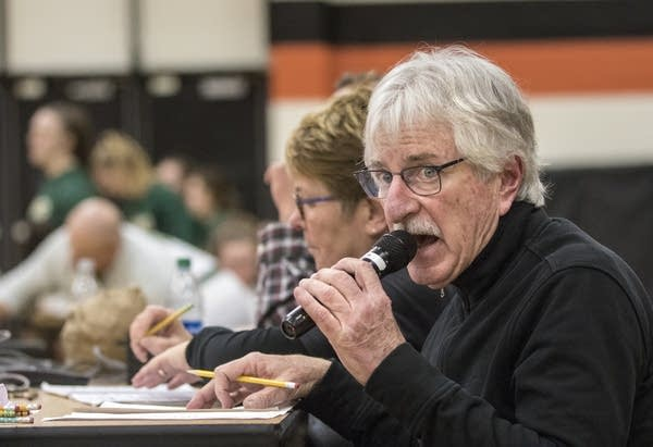 A man speaks into a microphone in a high school gym.