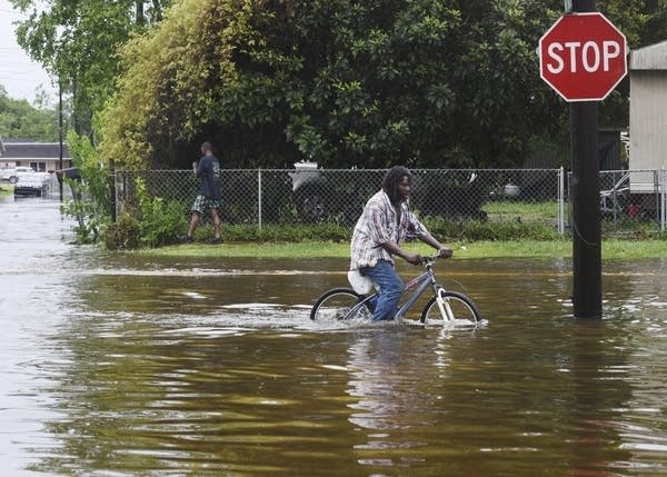 A man tries to bike through the flooding from the rains of storm Barry.