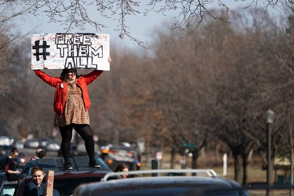 A woman stands on top of a car with a sign.