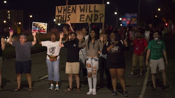 Protesters stand on I-94, ignoring police orders.