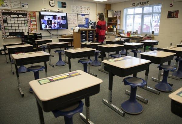 Desks sit empty as a teacher talks in front of a screen.