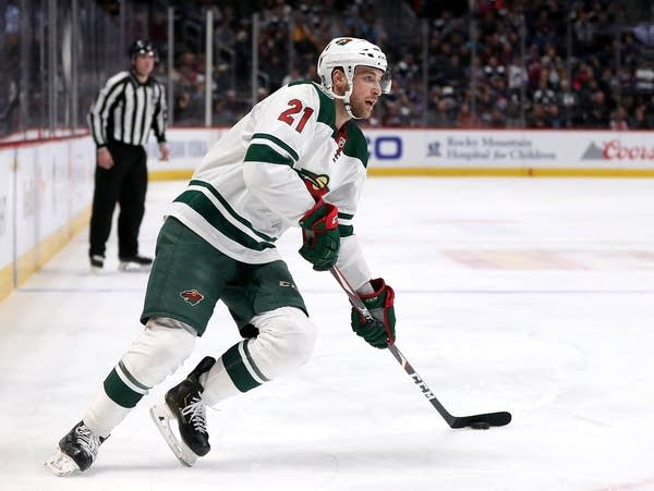 Minnesota wild player skates on ice with the puck.