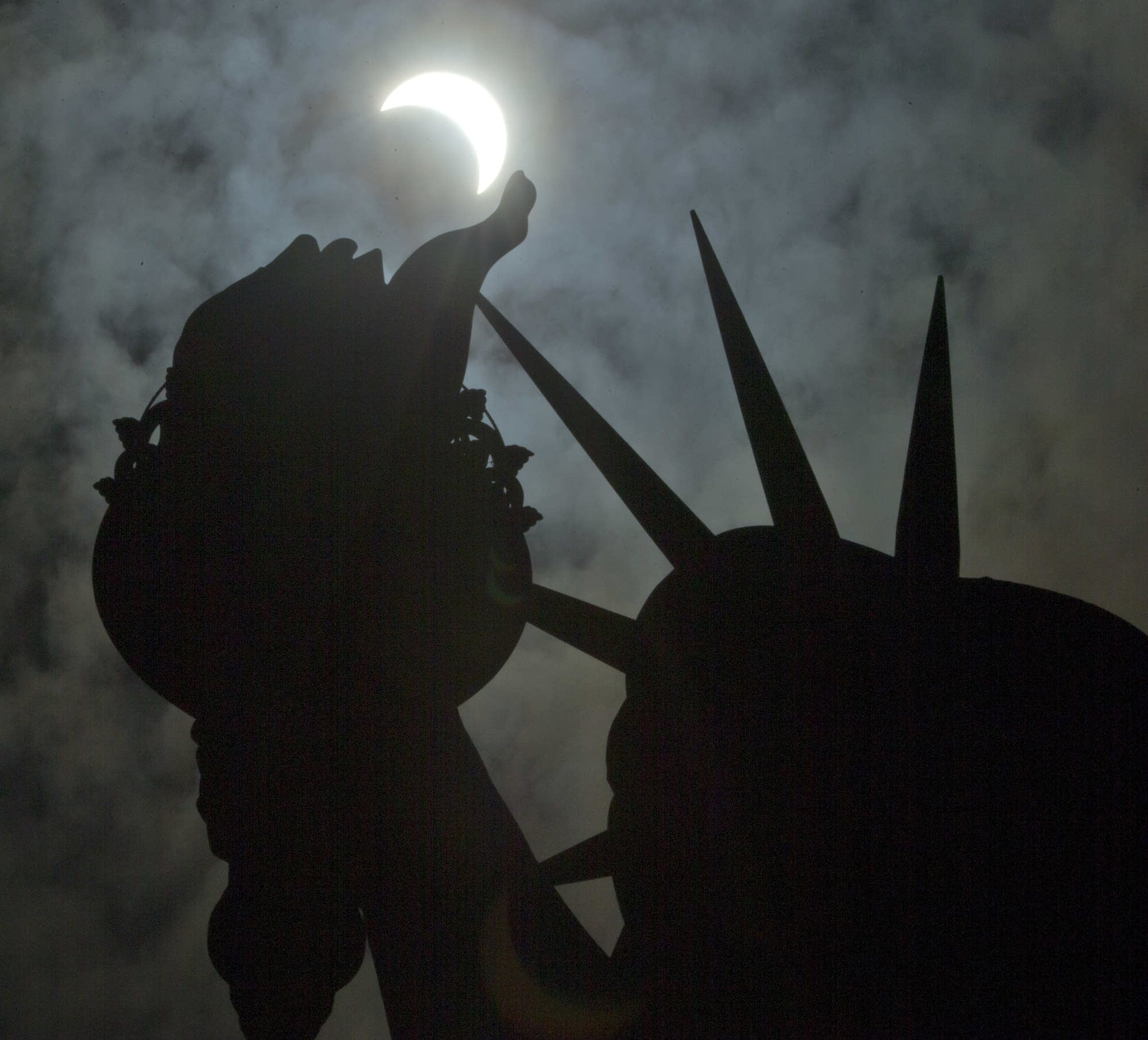 A view of the partial solar eclipse hangs above the Statue of Liberty.