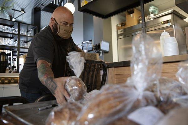 A man puts bread in a paper bag.