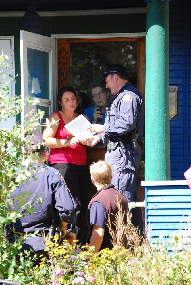 Police show a search warrant to Sarah Coffey
