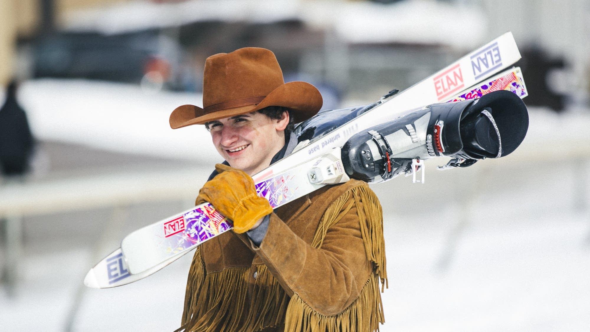 Dakota Morris carries his skis toward the starting line.
